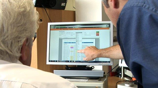 Two men working using the Assure System on a PC
